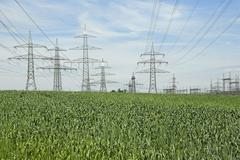 Grain field with electricity pylons and transformer station Stock Photos