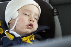 Young boy, 18 months, sleeping in a car seat Stock Photos