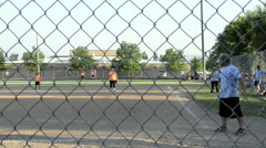 Small town, USA annual coed softball tournament viewed through the backstop Stock Footage