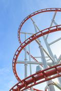 loops of roller coaster under blue sky - stock photo
