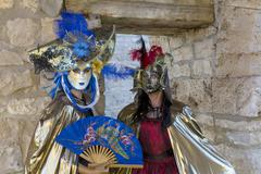 Two women wearing Venetian masks and costumes - stock photo