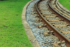 railway and green grass beside - stock photo