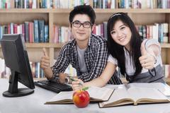 Cheerful students showing thumbs-up Stock Photos