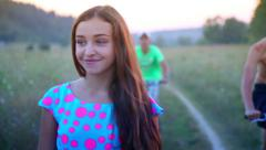 Young, beautiful, cheerful girl shyly looks at adolescent boys. Stock Footage