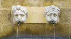 Two carved heads on fountain Aix en Provence Bouches du Rhone Stock Photos