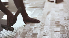 Carpenter worker installing wood parquet board with a hammer Stock Footage