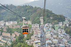 Gondola of a cable car and the town of Gangtok aerial view Sikkim Himalayas - stock photo
