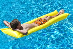 Boy 12 years lying on a lilo in a swimming pool Stock Photos