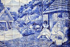 Azulejo painted tiles two women doing embroidery work Madeira Portugal Europe Stock Photos