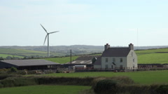Wind turbine near farm house, anglesey, north wales, uk Stock Footage