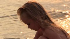 Girl Play, seat and get up at Sunset Evening Beach. Slow motion. Stock Footage