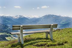 Stock Photo of wooden bench with views of the alps, brixen im thale, tyrol austria