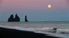 Full moon rising over Reynisdrangar, Iceland, scenic rugged beach Stock Footage