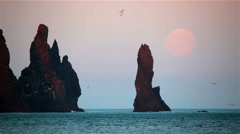 Full moon rising next to Reynisdrangar, Iceland, scenic rugged beach Stock Footage