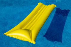 Yellow lilo in a swimming pool - stock photo
