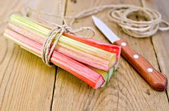 rhubarb with coil of rope and knife on board - stock photo