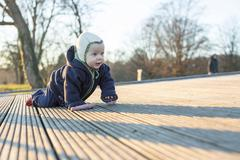 Baby 9 months crawling over a wooden floor Konstanz Baden Wurttemberg Germany - stock photo