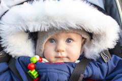 Baby 9 months wearing a thick jacket - stock photo
