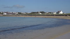 Waves lap beach at trearddur bay, anglesey, wales, uk Stock Footage