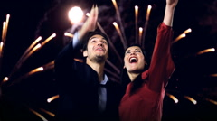 Young couple looking at new year's fireworks Stock Footage