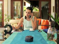 Young businesswoman talking oc cellphone while drinking coffee NTSC Stock Footage