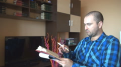 Portrait of young student learning home, reading book writing in notebook, exams Stock Footage