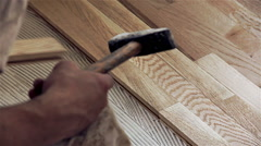Carpenter worker installing wood parquet board during flooring from the top Stock Footage