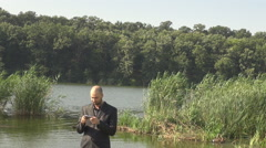 Portrait of business man outdoors, sending email from smart phone, man in nature Stock Footage
