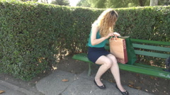 Blonde woman shopaholic with shopping bags and dress outside, happy for buying - stock footage