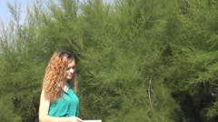 Stressful day for young blonde woman, frowned walking in park near green trees  - stock footage