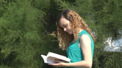 Beautiful blonde curly woman outside, reading a book, relaxation in green nature Stock Footage