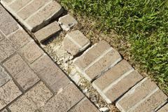Close Up Of a Brick Walkway Edge In Need Of Repair - stock photo