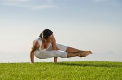 Young woman practising Hatha yoga here the pose kakasana bakasana Stock Photos