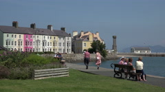People sit and relax on the promenade at beaumaris, anglesey, wales, uk Stock Footage