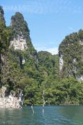 Forested karst limestone mountains with jungle vegetation rising from the water - stock photo
