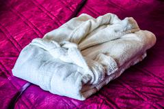 white bathrobe on the bed in hotel room - stock photo