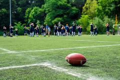 American football on field with team in background Stock Photos