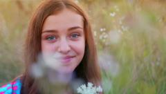 A young girl sitting in the grass in nature and have fun looking at the camera. Stock Footage
