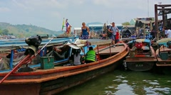 Ranong, thailand - circa mar 2014: tourists sit in old wooden boats Stock Footage