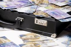 briefcase full of swiss francs, bills - stock photo