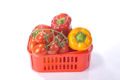tomatoes (solanum lycopersicum) and bell peppers (capsicum) in a red plastic  - stock photo