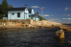Holiday houses along the rocky shore of the st. lawrence river, tadoussac, ca Stock Photos