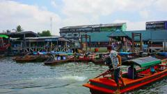 Ranong, thailand - circa mar 2014: pier with passengers and a lot of wooden b Stock Footage