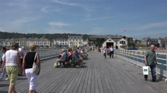 Tourists walk along the pier in beaumaris, anglesey, wales, uk Stock Footage