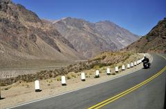 motorcyclist in the andes on the road ra7, ruta nacional 7, between mendoza,  - stock photo