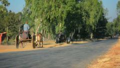 Bagan area, myanmar- 12 jan 2014: man transport fresh water in big barrels on Stock Footage