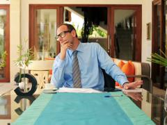 Bored young businessman sitting by table in luxury home NTSC Stock Footage
