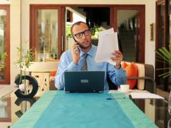 Angry, furious businessman talking on cellphone by table in luxury home NTSC Stock Footage
