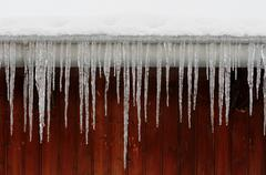 Icicles on eaves Stock Photos