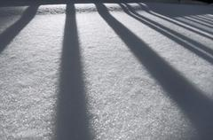 Winter impression, fence casting a shadow on snow Stock Photos
